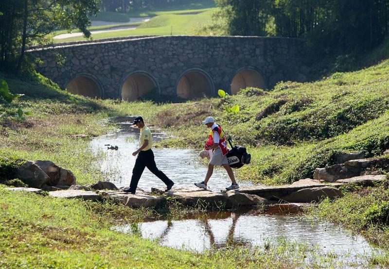 SHENZHEN, CHINA - NOVEMBER 27:  Martin Kaymer of Germany and caddie Justin Grenfell-Hoyle  walk over a stone bridge during the first round of the Omega Mission Hills World Cup at the Mission Hills Resort on November 27, 2008 in Shenzhen, China.  (Photo by Stuart Franklin/Getty Images)