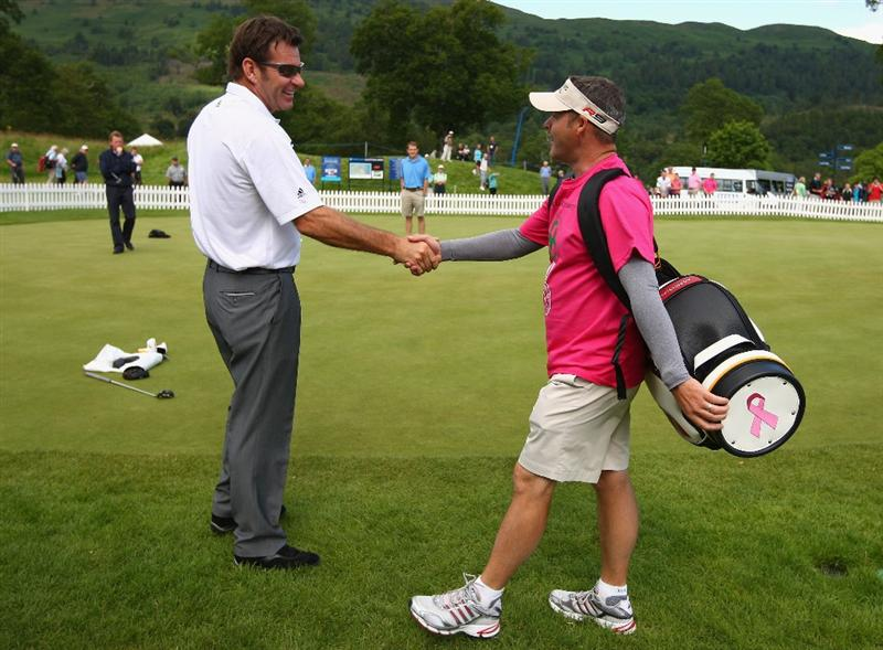 LUSS, SCOTLAND - JULY 09:  Caddy Billy Foster shakes hands with Sir Nick Faldo as he embarks on his Sponsored Walk to Turnberry for the Darren Clarke Foundation and the Candlelighters Children's Cancer Trust during the First Round of The Barclays Scottish Open at Loch Lomond Golf Club on July 09, 2009 in Luss, Scotland.  (Photo by Richard Heathcote/Getty Images)