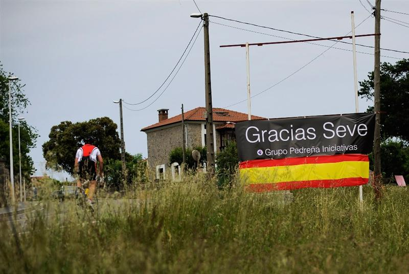PEDRENA, SPAIN - MAY 10:  A cyclist rides beside a banner that reads 'Thanks Seve'  hung at the entrance of Pedrena in preparation for the funeral service of legendary Spanish golfer Seve Bellesteros on May 10, 2011 in Pedrena, Spain.  (Photo by David Ramos/Getty Images)