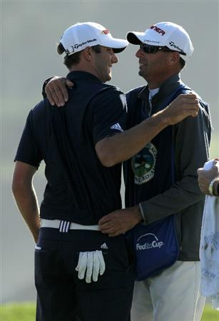 PEBBLE BEACH, CA - FEBRUARY 14:  Dustin Johnson hugs his caddie after making the winning putt on the 18th hole during the final round of the AT&T Pebble Beach National Pro-Am at Pebble Beach Golf Links on February 14, 2010 in Pebble Beach, California.  (Photo by Stephen Dunn/Getty Images)
