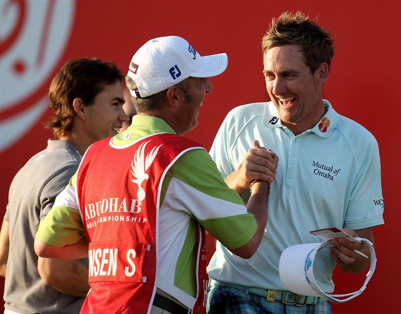 ABU DHABI, UNITED ARAB EMIRATES - JANUARY 21:  Ian Poulter of England and Soren Hansen's caddie Phil Morbey on the 18th green during the first round of the Abu Dhabi Golf Championship at Abu Dhabi Golf Club on January 21, 2010 in Abu Dhabi, United Arab Emirates.  (Photo by Ross Kinnaird/Getty Images)