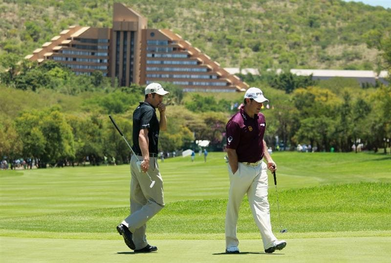 SUN CITY, SOUTH AFRICA - DECEMBER 04:  Englishmen Ross Fisher and Lee Westwood cross paths on the first green during the third round of the 2010 Nedbank Golf Challenge at the Gary Player Country Club Course  on December 4, 2010 in Sun City, South Africa.  (Photo by Warren Little/Getty Images)