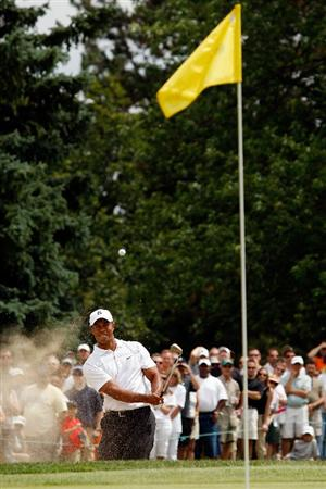 GRAND BLANC, MI - AUGUST 01:  Tiger Woods chips out of a bunker on the 7th hole during round three of the Buick Open at Warwick Hills Golf and Country Club on August 1, 2009 in Grand Blanc, Michigan.  (Photo by Chris Graythen/Getty Images)