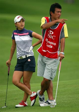 SINGAPORE - MARCH 04:  Momoko Ueda of Japan waits with her caddie on the 16th hole during the Pro-Am prior to the start of the HSBC Women's Champions at Tanah Merah Country Club on March 4, 2009 in Singapore.  (Photo by Andrew Redington/Getty Images)