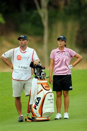 KUALA LUMPUR, MALAYSIA - OCTOBER 22:  Hee-Won Han of Korea Republic stands with her caddie and waits for her turn to play on the 8th hole during Round One of the Sime Darby LPGA on October 22, 2010 at the Kuala Lumpur Golf and Country Club in Kuala Lumpur, Malaysia. (Photo by Stanley Chou/Getty Images)