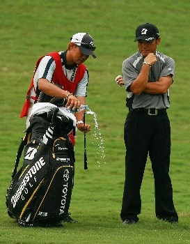 PORT SAINT LUCIE, FL - OCTOBER 26:  Shigeki Maruyama of Japan watches his caddie clean a club with bottled water in the fairway on the 18th hole during the second round of the Ginn Sur Mer Classic at Tesoro on October 26, 2007 in Port Saint Lucie, Florida.  (Photo by Doug Benc/Getty Images)
