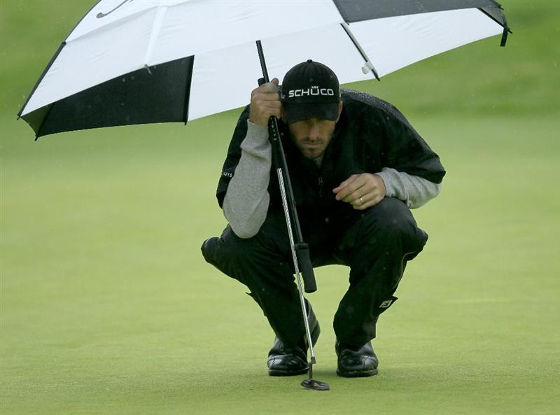 PACIFIC PALISADES, CA - FEBRUARY 18: Geoff Ogilvy of Australia holds his umbrella as he lines up his putt on the 11th hole during round two of the Northern Trust Open at Riviera Country Club on February 18, 2011 in Pacific Palisades, California.  (Photo by Stephen Dunn/Getty Images)