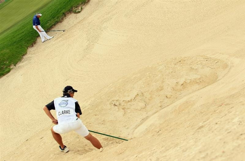 BAHRAIN, BAHRAIN - JANUARY 29:  Darren Clarke of Northern Ireland and his caddie both rake a bunker on the tenth hole during the third round of the Volvo Golf Champions at The Royal Golf Club on January 29, 2011 in Bahrain, Bahrain.  (Photo by Andrew Redington/Getty Images)