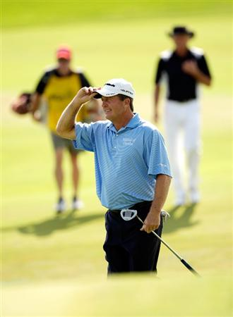 CARMEL, IN - AUGUST 02:  Fred Funk of the USA tips his hat to the crowd on the 16th hole as Greg Norman of Australia walks behind during the 2009 U.S. Senior Open on August 2, 2009 at Crooked Stick Golf Club in Carmel, Indiana.  (Photo by Jamie Squire/Getty Images)
