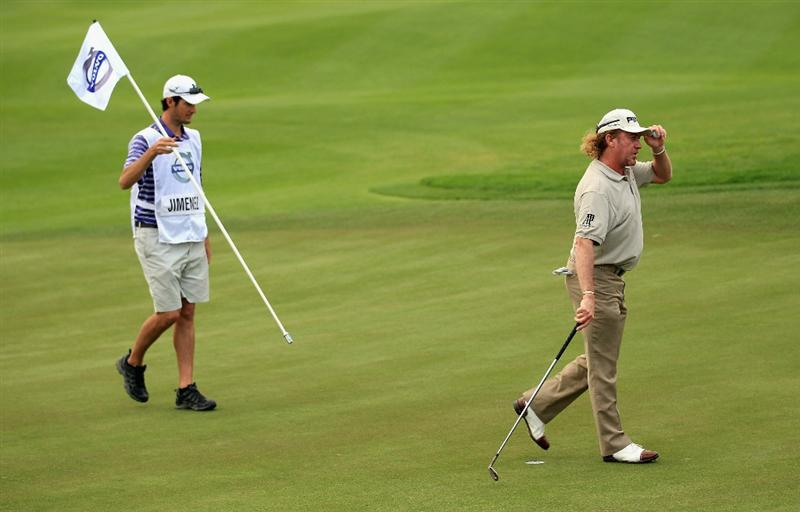 BAHRAIN, BAHRAIN - JANUARY 28:  Miguel Angel Jimenez of Spain waves to the crowd on the 18th green as his caddie Michael Hough looks on during the second round of the Volvo Golf Champions at The Royal Golf Club on January 28, 2011 in Bahrain, Bahrain.  (Photo by Andrew Redington/Getty Images)