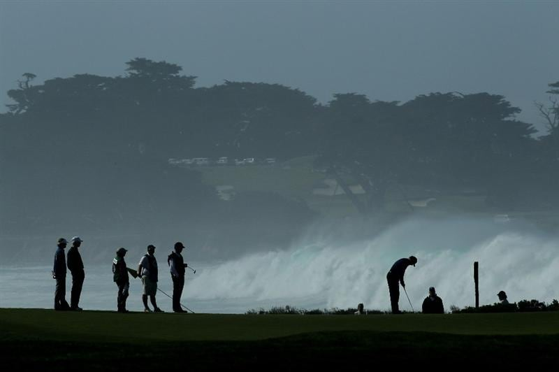 PEBBLE BEACH, CA - FEBRUARY 13:  A group putts out on the 13th green with high surf in the background during the third round of the AT&T Pebble Beach National Pro-Am at Monterey Peninsula Country Club on February 13, 2010 in Pebble Beach, California. (Photo by Stephen Dunn/Getty Images)