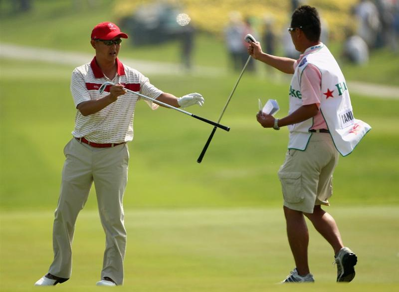 BANGKOK, THAILAND - JANUARY 10:  Toru Taniguchi of Japan exchanges clubs during the fourball match on Day two of The Royal Trophy at the Amata Spring Country Club on January 10, 2009 in Bangkok, Thailand.  (Photo by Ian Walton/Getty Images)