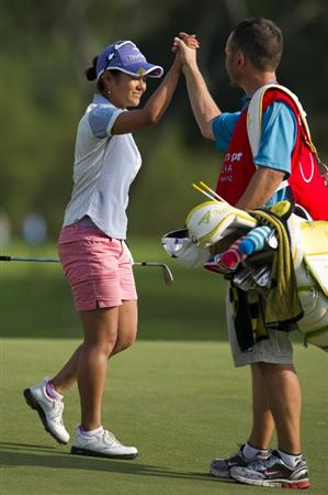 CHON BURI, THAILAND - FEBRUARY 21:  Ai Miyazato of Japan celebrates with her caddy after sinking a chip shot on the 18th green during the final round of the Honda PTT LPGA Thailand at Siam Country Club on February 21, 2010 in Chon Buri, Thailand.  (Photo by Victor Fraile/Getty Images)