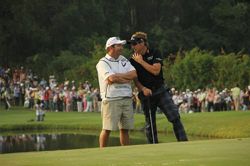 HONG KONG - NOVEMBER 21:  Ian Poulter of England speaks to his caddie before playing his last putt on the 18th hole during day four of the UBS Hong Kong Open at The Hong Kong Golf Club on November 21, 2010 in Hong Kong, Hong Kong.  (Photo by Stanley Chou/Getty Images)