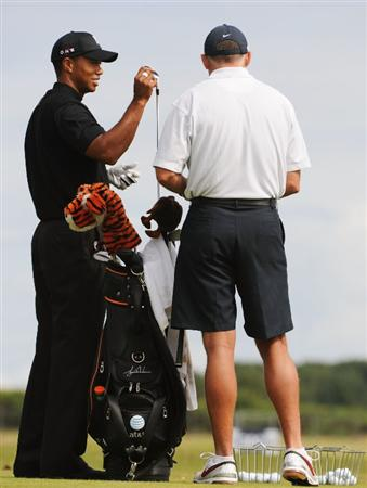 TURNBERRY, SCOTLAND - JULY 15:  Tiger Woods of USA pulls a club as caddy Steve Williams looks on during a practice round prior to the 138th Open Championship on the Ailsa Course, Turnberry Golf Club on July 15, 2009 in Turnberry, Scotland.  (Photo by Harry How/Getty Images)