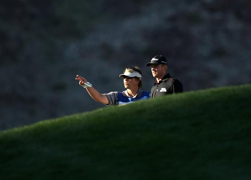 LA QUINTA, CA - JANUARY 25:  John Merrick and his caddy consult on the 14th fairway on the Palmer Private course at PGA West during the final round of the Bob Hope Chrysler Classic on January 25, 2009 in La Quinta, California.  (Photo by Stephen Dunn/Getty Images)