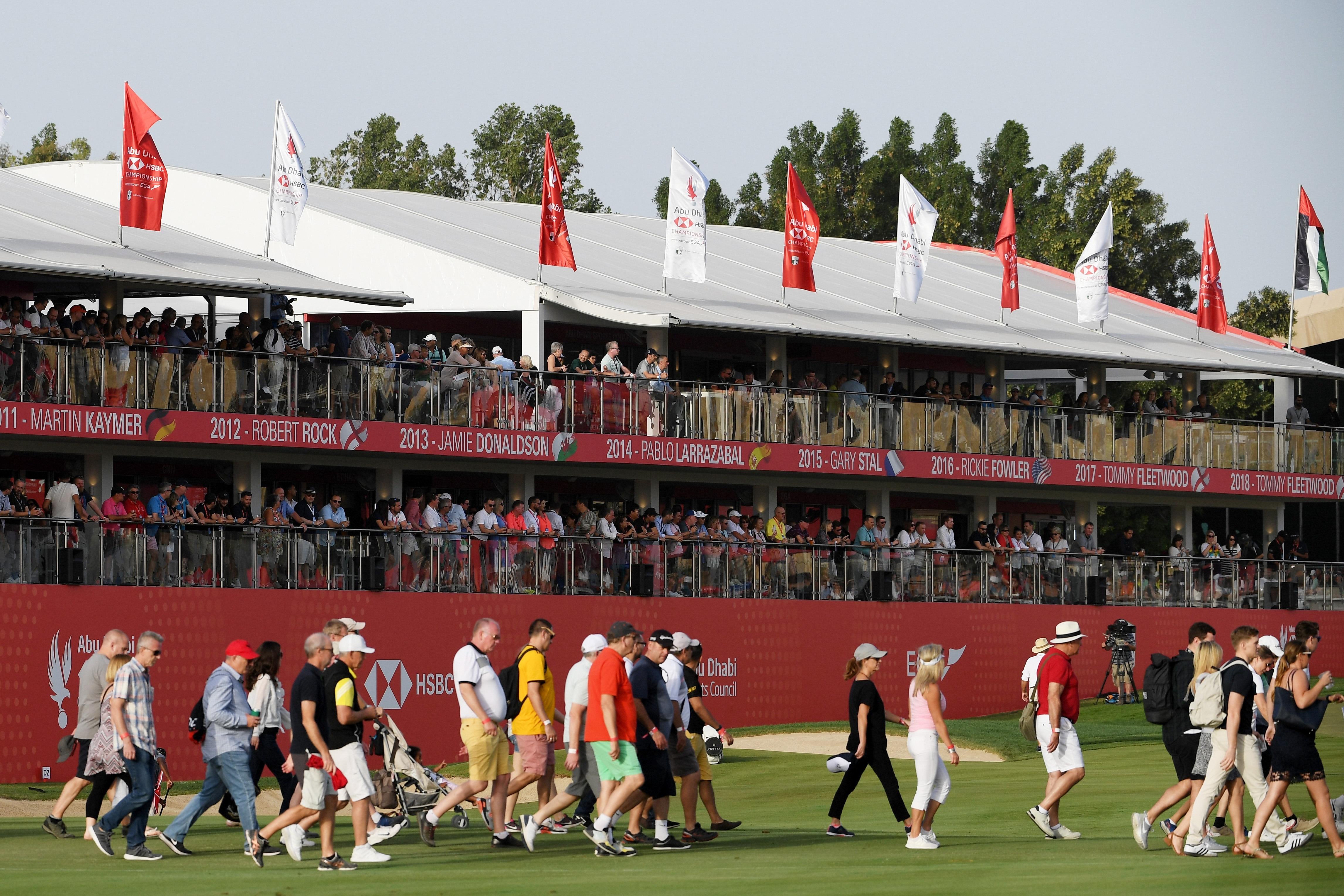 Fans walk down 18th hole at Abu Dhabi Golf Club