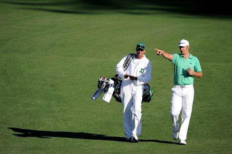 AUGUSTA, GA - APRIL 07:  Dustin Johnson points as he talks to his caddie Robert Gregory Brown on the second hole fairway during the first round of the 2011 Masters Tournament at Augusta National Golf Club on April 7, 2011 in Augusta, Georgia.  (Photo by Harry How/Getty Images)