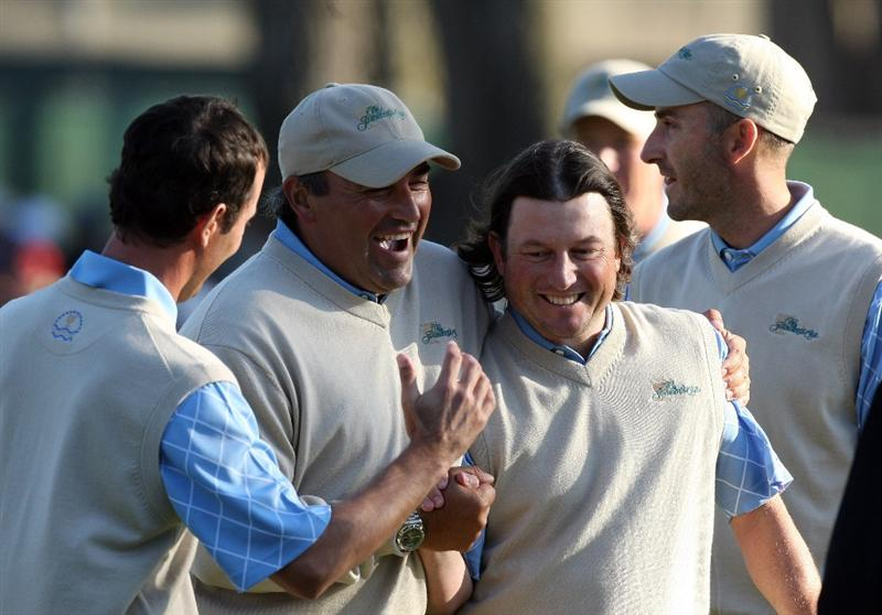 SAN FRANCISCO - OCTOBER 09:  Angel Cabrera of Argentina and the International Team gets hold of Tim Clark of South Africa after Clark had just holed a great eagle putt at the 18th hole to win his match with Vijay Singh against Cink and Glover of the USA Team during the Day Two Fourball Matches in The Presidents Cup at Harding Park Golf Course on October 9, 2009 in San Francisco, California  (Photo by David Cannon/Getty Images)
