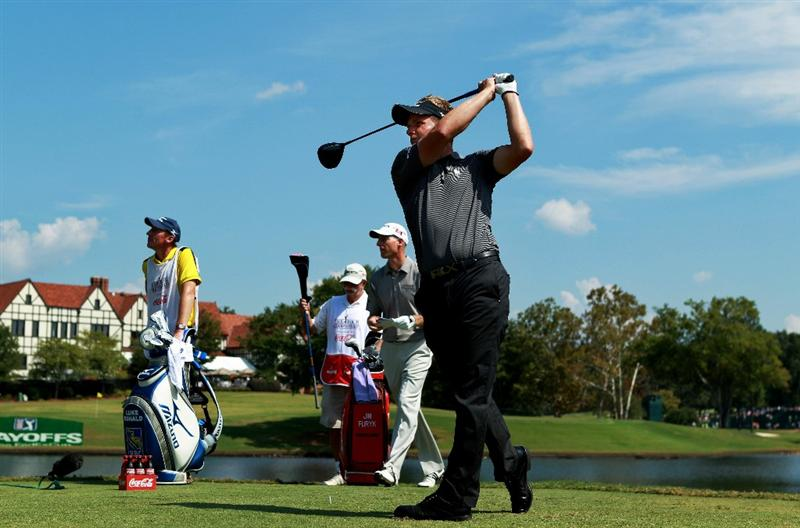 ATLANTA - SEPTEMBER 25:  Luke Donald of England (R) hits his tee shot on the seventh hole while Jim Furyk (2nd R), caddie John McLaren (L) and caddie Mike 'Fluff' Cowan (2nd L) look on during the third round of THE TOUR Championship presented by Coca-Cola at East Lake Golf Club on September 25, 2010 in Atlanta, Georgia.  (Photo by Scott Halleran/Getty Images)
