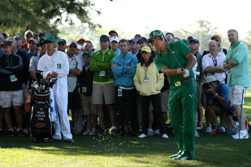 AUGUSTA, GA - APRIL 07:  Rickie Fowler plays a shot from the rough on the first hole as his caddie Joe Skovron looks on during the first round of the 2011 Masters Tournament at Augusta National Golf Club on April 7, 2011 in Augusta, Georgia.  (Photo by Andrew Redington/Getty Images)