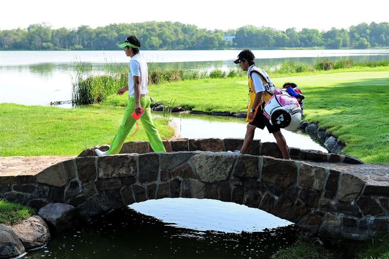 CHASKA, MN - AUGUST 14:  Ryo Ishikawa of Japan walks with his caddie Hiroyuki Kato across a bridge on the 16th hole during the second round of the 91st PGA Championship at Hazeltine National Golf Club on August 14, 2009 in Chaska, Minnesota.  (Photo by Stuart Franklin/Getty Images)