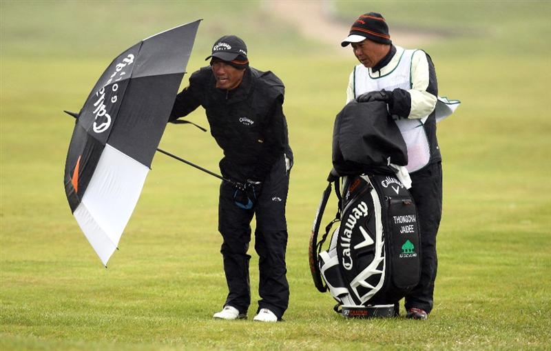 BALTRAY, IRELAND - MAY 16:  Thongchai Jaidee of Thailand takes cover during the third round of The 3 Irish Open at County Louth Golf Club on May 16, 2009 in Baltray, Ireland.  (Photo by Ross Kinnaird/Getty Images)