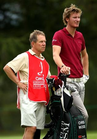 CRANS, SWITZERLAND - SEPTEMBER 03:  Chris Wood of England waits with his caddie Dave McNeilly on the 18th hole during the first round of The Omega European Masters at Crans-Sur-Sierre Golf Club on September 3, 2009 in Crans Montana, Switzerland.  (Photo by Andrew Redington/Getty Images)