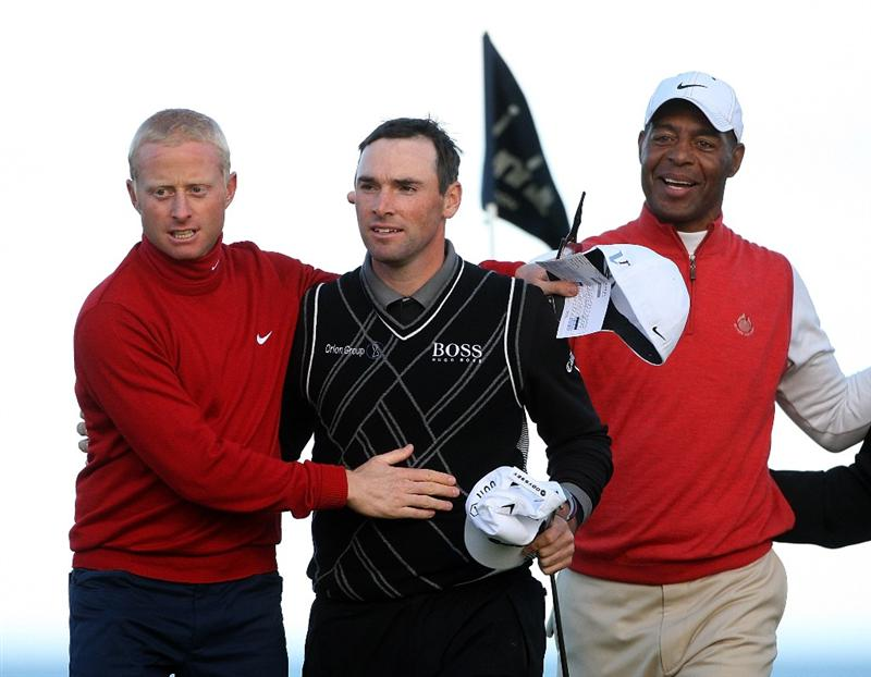 KINGSBARNS, SCOTLAND - OCTOBER 04:  Simon Dyson of England (left) is congratulated by Oliver Wilson and Marcus Allen on the 18th green after he finishes his round during the third round of The Alfred Dunhill Links Championship at Kingsbarns Golf Links on October 4, 2009 in Kingsbarns, Scotland.The third round was postponed on Saturday due to gale force winds.  (Photo by Andrew Redington/Getty Images)