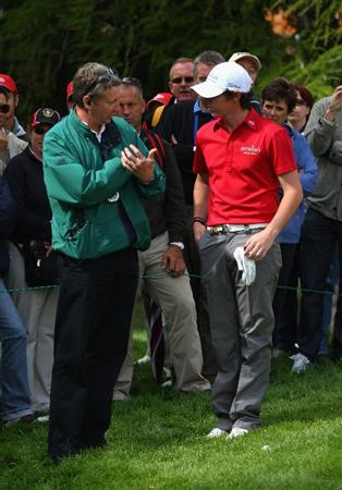 CRANS, SWITZERLAND - SEPTEMBER 07:  Rory McIlroy of Northern Ireland talks with a referee after his ball ended up in the crook of a spectator's arm on the first hole during the final round of the Omega European Masters at Crans-Sur-Sierre Golf Club on September 7, 2008 in Crans Montana, Switzerland.  (Photo by Andrew Redington/Getty Images)