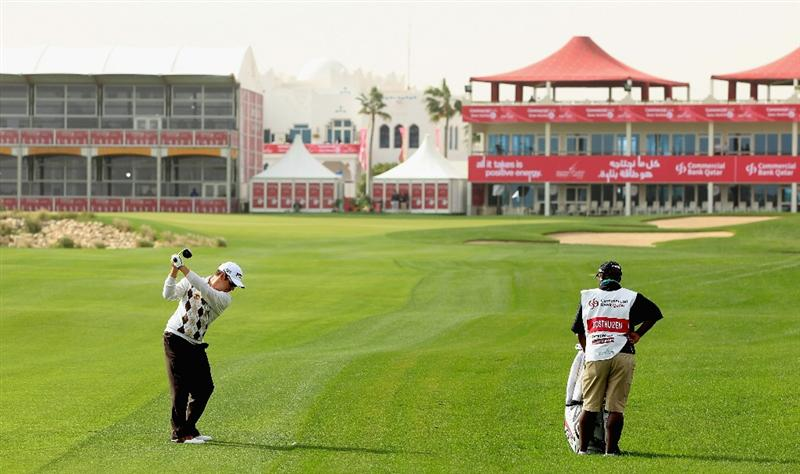 DOHA, QATAR - FEBRUARY 03:  Louis Oosthuizen of South Africa hits his second shot on the 18th hole as his caddie Zack Rasego looks on during the first round of the Commercialbank Qatar Masters held at Doha Golf Club on February 3, 2011 in Doha, Qatar.  (Photo by Andrew Redington/Getty Images)