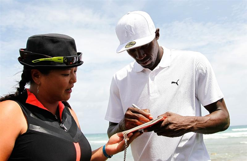 MONTEGO BAY, JAMAICA - APRIL 16:  Usain Bolt signs an autograph for Christina Kim of the United States during the semifinal matches of The Mojo 6 Jamaica LPGA Invitational at Cinnamon Hill Golf Course on April 16, 2010 in Montego Bay, Jamaica.  (Photo by Kevin C. Cox/Getty Images)