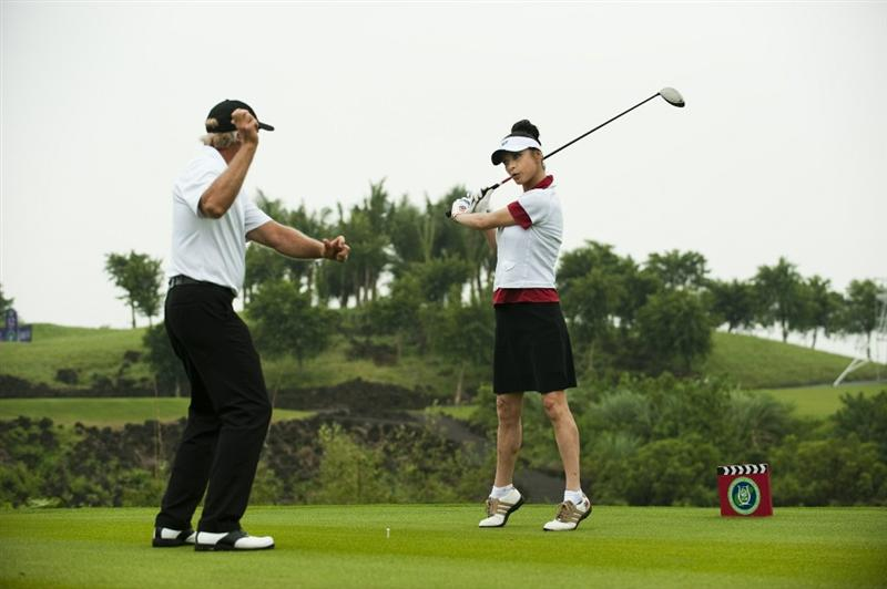 HAIKOU, CHINA - OCTOBER 27:  Golf legend Greg Norman teaches Oscar-winning actress Catherine Zeta-Jones during practice ahead of the inaugural Mission Hills Star Trophy on October 27, 2010 in Haikou, China.  The Mission Hills Star Trophy is Asia's leading leisure liflestyle event and features Hollywood celebrities and international golf stars.  (Photo by Victor Fraile/Getty Images)