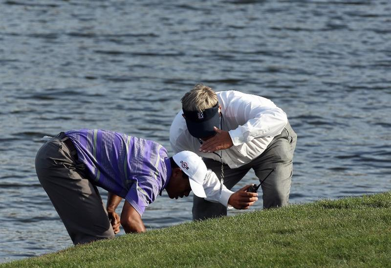 ORLANDO, FL - MARCH 28:  Tiger Woods of the USA searches for his ball as PGA Tour Rules Official John Lillvis checks if his 5 minutes is up before declaring his ball lost in the hazard at the 18th hole during the third round of the Arnold Palmer Invitational Presented by Mastercard at the Bay Hill Club and Lodge on March 28, 2009 in Orlando, Florida  (Photo by David Cannon/Getty Images)