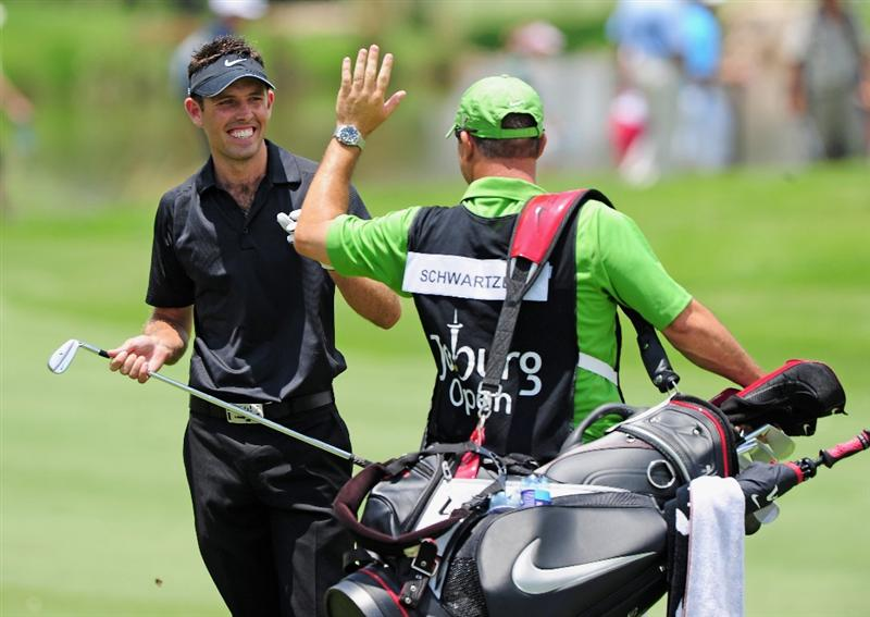 JOHANNESBURG, SOUTH AFRICA - JANUARY 17:  Charl Schwartzel of South Africa (L) celebrates with his caddie on the 14th hole during the final round of the Joburg Open at Royal Johannesburg and Kensington Golf Club on January 17, 2010 in Johannesburg, South Africa.  (Photo by Stuart Franklin/Getty Images)