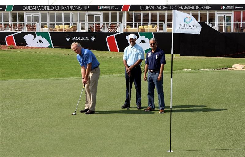 DUBAI, UNITED ARAB EMIRATES - NOVEMBER 18:  Greg Norman, designer of the Earth Course, takes a putt whilst being watched by Jeev Milka Singh of India and Saeed Harib of Nakheel Leisure at the official course opening prior to the start of the Dubai World Championship on the Earth Course, Jumeirah Golf Estates on November 18, 2009 in Dubai, United Arab Emirates.  (Photo by Andrew Redington/Getty Images)