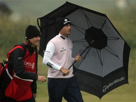 SOUTHPORT, UNITED KINGDOM - JULY 18:  Steve Webster of England and his caddie Jan Squire shield themselves from the rain during the second round of the 137th Open Championship on July 18, 2008 at Royal Birkdale Golf Club, Southport, England.  (Photo by David Cannon/Getty Images)