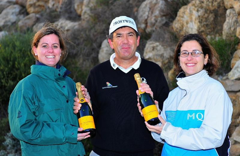 ESTORIL, PORTUGAL - APRIL 02:  David Frost of South Africa is presented with two bottles of champange in recognition of his hole in one on the 12th hole, by Sam White, Tournament Service Manager (left) and Gaia Zonchello, Tournament Secretary (right) after the first round of The Estoril Open de Portugal The Oitavos Dunes Golf Course on April 2, 2009 in Cascais, Portugal.  (Photo by Stuart Franklin/Getty Images)