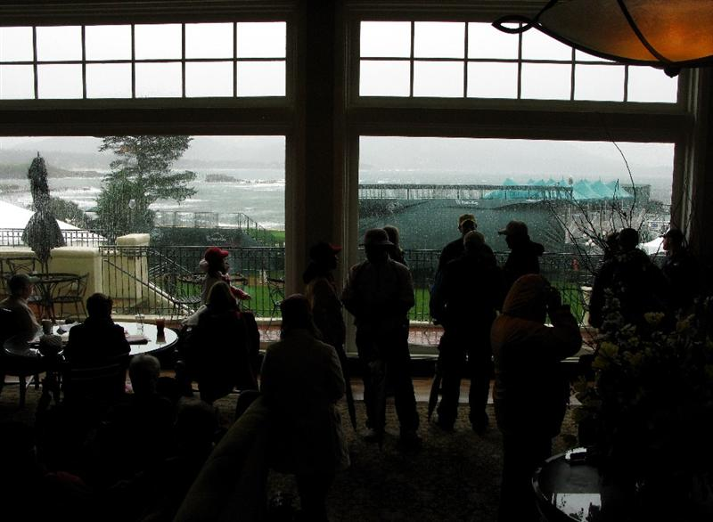PEBBLE BEACH, CA - FEBRUARY 15:   People wait in a lounge in the Lodge  at Pebble Beach overlooking the 18th hole during a weather delay before the final round of the AT&T Pebble Beach National Pro-Am at Pebble Beach Golf Links on February 15, 2009 in Pebble Beach, California. (Photo by Stephen Dunn/Getty Images)