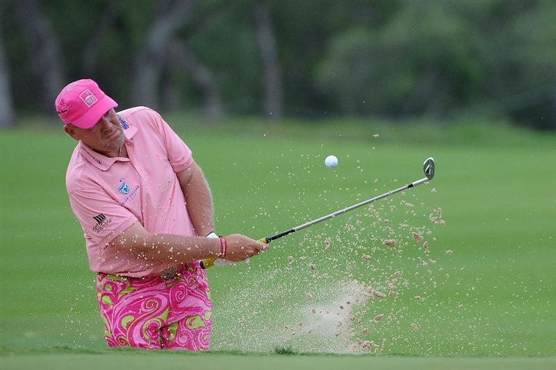 SAN ANTONIO, TX- MAY 13:  John Daly hits out of the greenside bunker on the  5th hole during the first round of the Valero Texas Open at the TPC San Antonio on May 13, 2010 in San Antonio, Texas. (Photo by Marc Feldman/Getty Images)