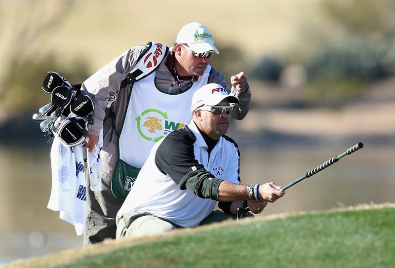 SCOTTSDALE, AZ - FEBRUARY 03:  Chris Couch lines up a putt with his caddie on the 15th hole green during the first round of the Waste Management Phoenix Open at TPC Scottsdale on February 3, 2011 in Scottsdale, Arizona.  (Photo by Christian Petersen/Getty Images)