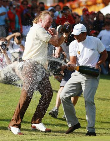 CRANS, SWITZERLAND - SEPTEMBER 05:  Miguel Angel Jimenez of Spain is covered in champagne on the 18th green by fellow coutryman Pablo Larrazabal after winning The Omega European Masters on a score of -21 under par at Crans-Sur-Sierre Golf Club on September 5, 2010 in Crans Montana, Switzerland.  (Photo by Warren Little/Getty Images)