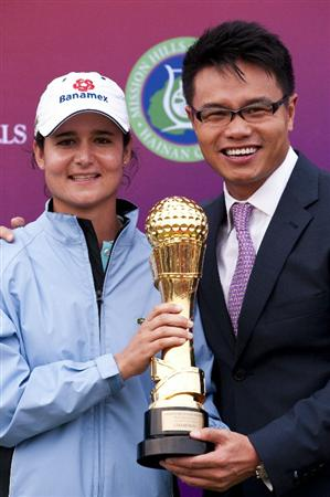 HAIKOU, CHINA - OCTOBER 31:  Lorena Ochoa (L) of Mexico poses with Dr. Ken Chu, Vice Chairman of Mission Hills Group after winning the Mission Hills Start Trophy at Mission Hills Resort on October 31, 2010 in Haikou, China.  The Mission Hills Star Trophy is Asia's leading leisure liflestyle event and features Hollywood celebrities and international golf stars.  (Photo by Victor Fraile/Getty Images for Mission Hills)