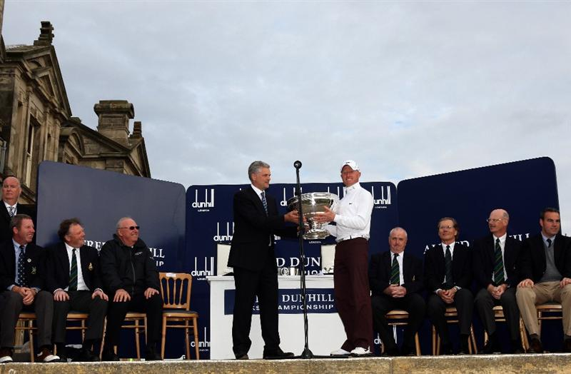 ST ANDREWS, SCOTLAND - OCTOBER 05:  Simon Dyson of England is presented with the trophy by Christopher Colfer, Chief executive of Alfred Dunhill after victory at the The Alfred Dunhill Links Championship at The Old Course on October 5, 2009 in St.Andrews, Scotland.  (Photo by Warren Little/Getty Images)