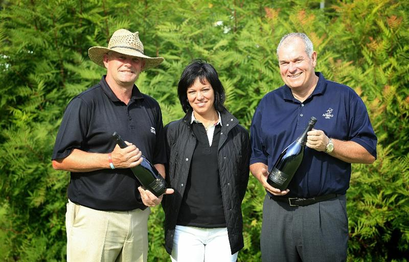 WOBURN, ENGLAND - SEPTEMBER 04:  England's Martin Poxon and David J Russell receive a bottle of Follador Spumanti Wine each from Mariachristina Follador for holing in one on the third hole during the second round of the Travis Perkins plc Senior Masters played on the Duke's Course, Woburn Golf Club on September 4, 2010 in Woburn, England.  (Photo by Phil Inglis/Getty Images)