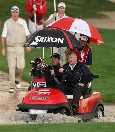 ABU DHABI, UNITED ARAB EMIRATES - JANUARY 15:  Henrik Stenson of Sweden makes his way back to the clubhouse in a buggy as rain halts play during the first round the Abu Dhabi Golf Championship at the Abu Dhabi Golf Club on January 15, 2009 in Abu Dhabi, United Arab Emirates.  (Photo by Ross Kinnaird/Getty Images)