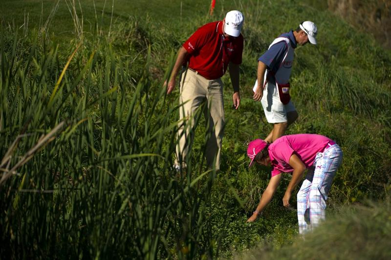 SAN MARTIN, CA - OCTOBER 14:  Rickie Fowler looks for his ball on the 18th hole with the help of a marshall and a caddie during the first round of the Frys.com Open at the Corde Valle Country Club on October 14, 2010 in San Martin, California.  (Photo by Robert Laberge/Getty Images)
