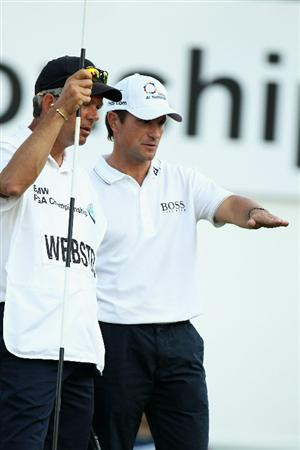 VIRGINIA WATER, ENGLAND - MAY 20:  Steve Webster of England talks with his caddie on the 18th green during the first round of the BMW PGA Championship on the West Course at Wentworth on May 20, 2010 in Virginia Water, England.  (Photo by Ross Kinnaird/Getty Images)
