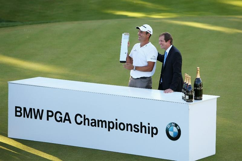 VIRGINIA WATER, ENGLAND - MAY 23:  Simon Khan (L) of England accepts the trophy from European Tour Chief Executive George O'Grady following his victory in the BMW PGA Championship on the West Course at Wentworth on May 23, 2010 in Virginia Water, England.  (Photo by Ian Walton/Getty Images)