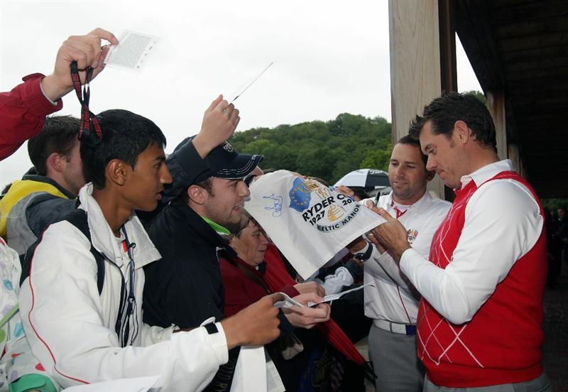 NEWPORT, WALES - OCTOBER 01:  Lee Westwood (R) of Europe signs autographs with Vice Captain Sergio Garcia as rain falls and play is suspended during the Morning Fourball Matches during the 2010 Ryder Cup at the Celtic Manor Resort on October 1, 2010 in Newport, Wales.  (Photo by Andrew Redington/Getty Images)